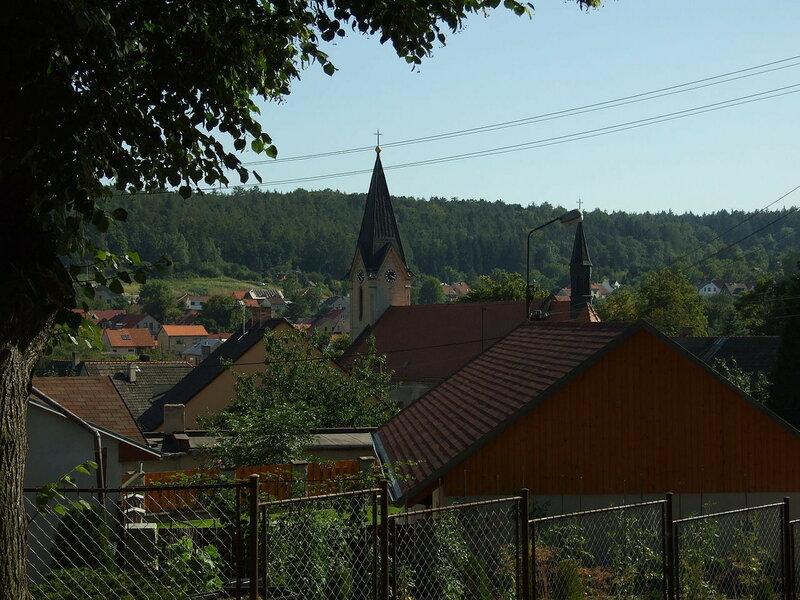 1280px-Libušín,_obec_a_kostelní_věž.JPG