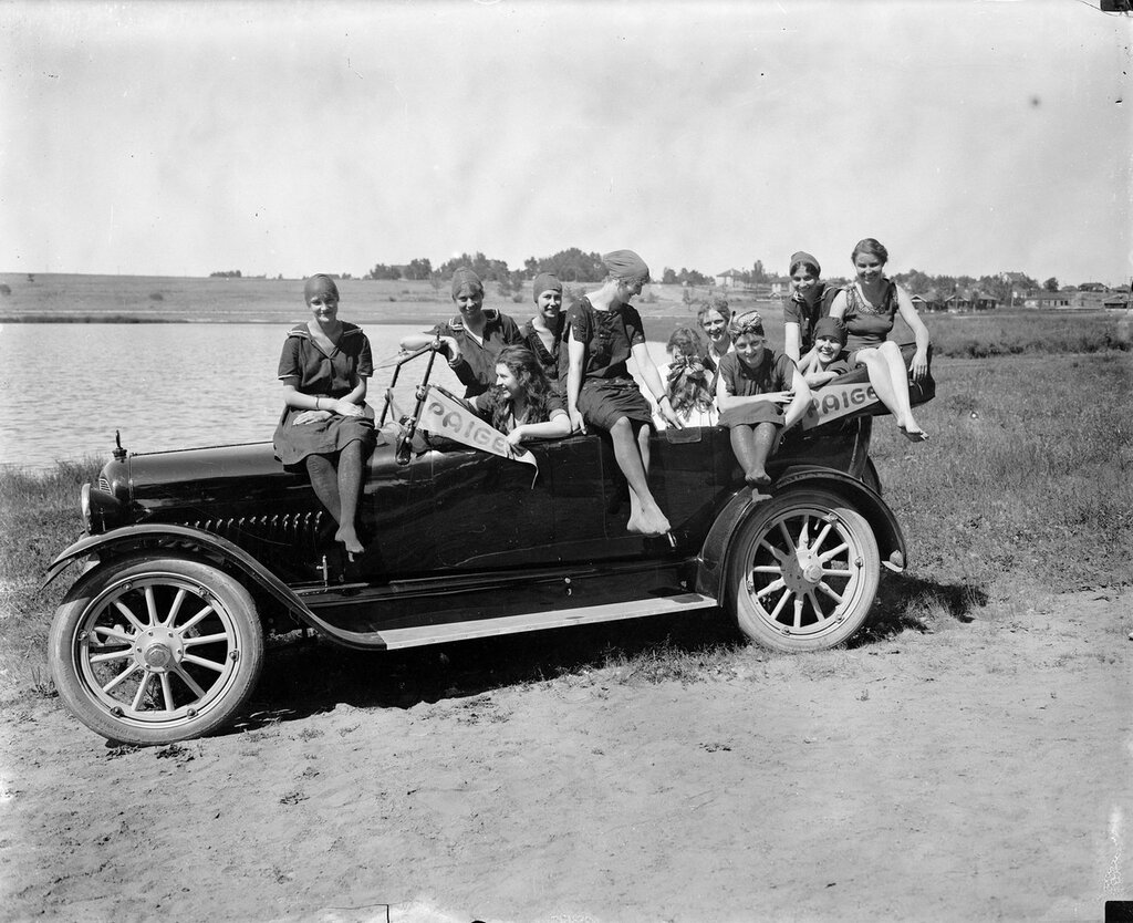 Women in bathing suits pose in an automobile, Denver, Colorado. Pennants reading 'Paige' also decorate the car. 1916