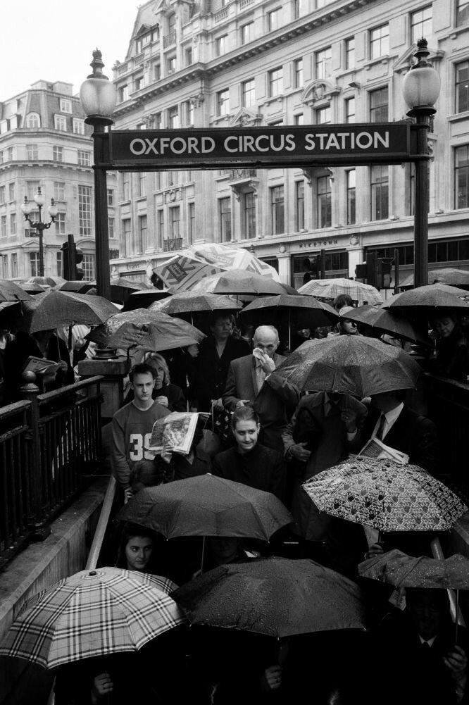 2001. В проливной дождь  городские жители спускаются на станцию метро «Площадь Оксфорд»