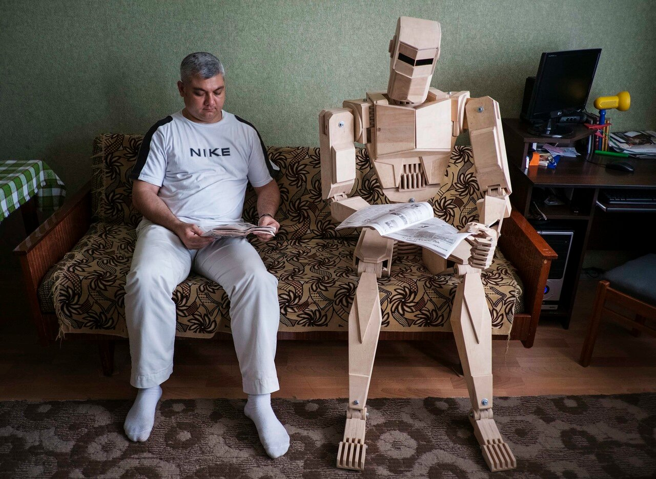 Ukrainian Dmitry Balandin poses with his wooden model Cylon in his flat in Zaporizhzhya