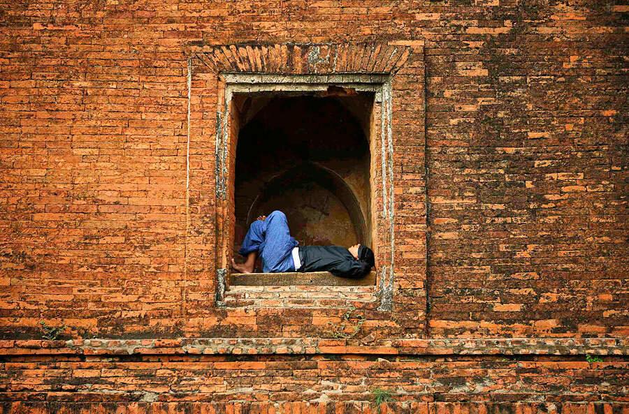 Мужчина спит на окне знаменитого буддийского храма 12-го века Дамаянги в историческом городе Баган, Мьянма.
