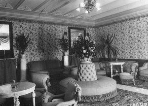Внутренний вид залы ожидания с цветами и мягкой мебелью.
