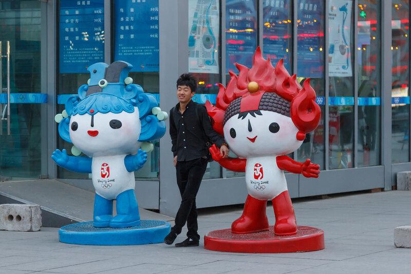 Китаец позирует с символами Пекинской олимпиады