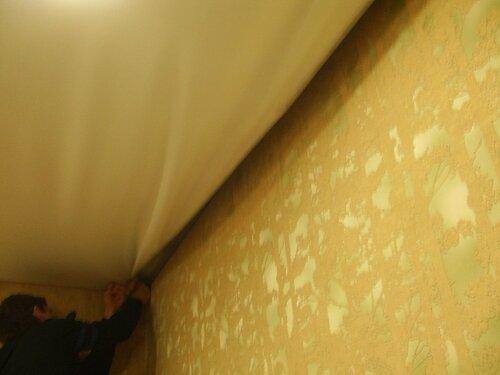 Фото 7. Плёнка натяжного потолка высвобождается по длинной части периметра помещения.