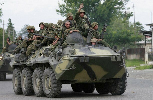 Soldiers travel on an armoured vehicle as part of a Russian military convoy on a main road close to Zugdidi