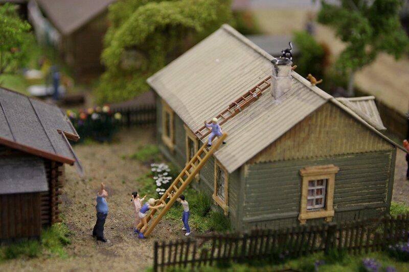 Гранд макет: дети при помощи лестницы хотят достать кота с трубы на крыше деревенского дома.