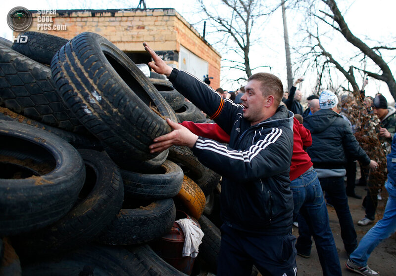 A pro-Russia protester throws a tyre on a barricade in front of an Ukrainian airbase in Kramatorsk