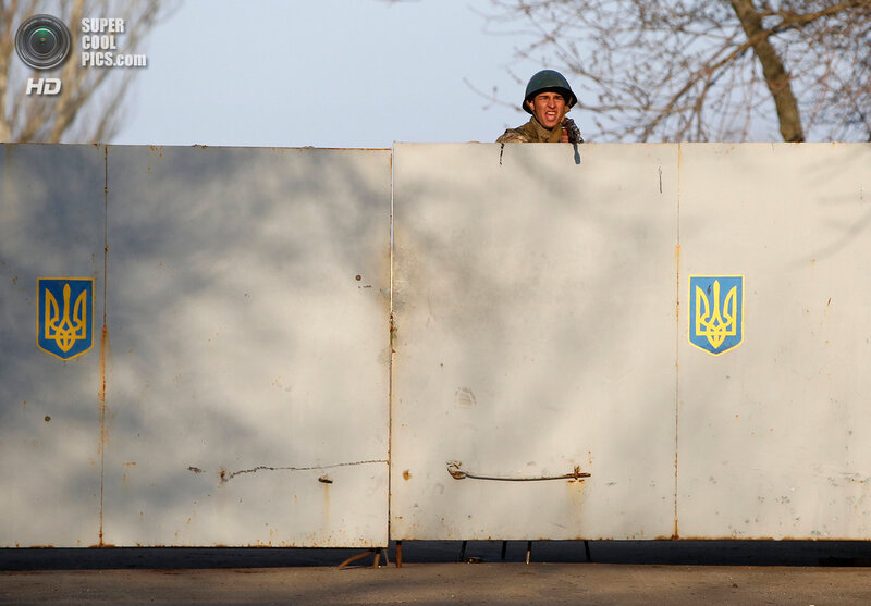 An Ukrainian soldier aims his rifle and shouts at pro-Russia protesters gathered in front of a Ukrainian airbase in Kramatorsk