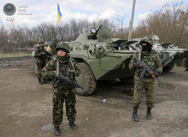 Ukrainian soldiers are seen near armored personnel carriers at a checkpoint near the town of Izium