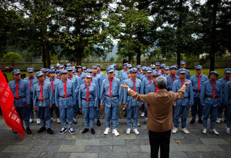 Ребенок, одетый в костюм солдата Красной Армии на коммунистической базе в Яньане и мужчина, показыва