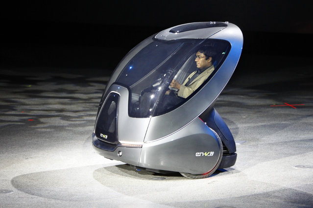 """An EN-V, or """"Electric Networked-Vehicle"""", is driven by a General Motors' staff member during an"""