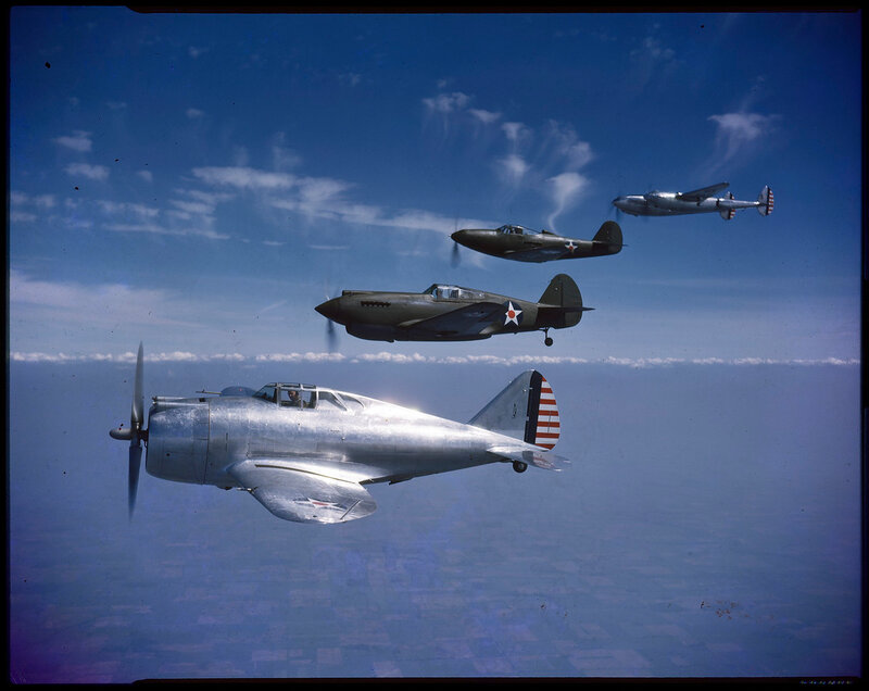 Aerial view of four United States Army Air Forces aircraft in flight in formation; bottom (foreground) to top (background): Republic YP-43 Lancer, Curtiss P-40 Warhawk, Bell P-39 Airacobra, and Lockheed P-38 Lightning; 1941.