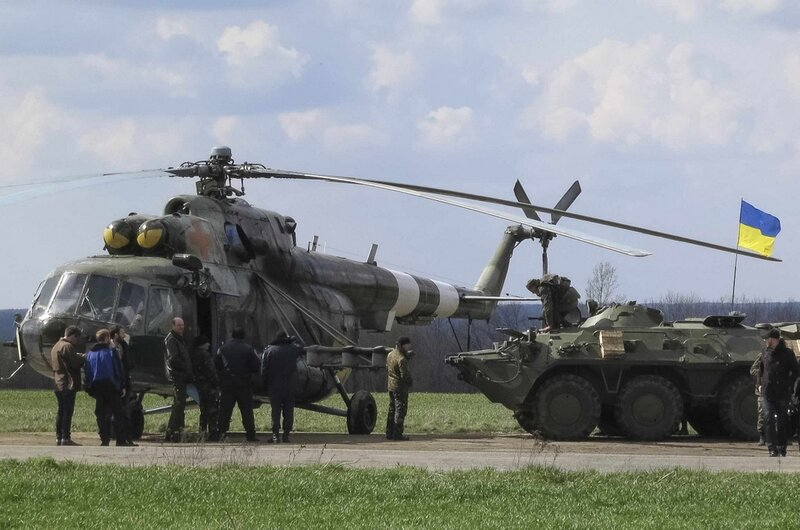 Ukrainian soldiers are seen near a MI-8 military helicopter and armored personnel carrier at a checkpoint near city of Izium