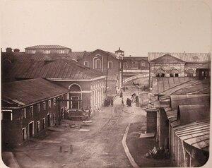 Вид зданий на территории Адмиралтейских Ижорских заводов (слева направо) магазин [товаров] 1-го сорта, магазин [товаров] 2-го сорта, мост через бассейн; большая слесарная [мастерская]; большая машинная [мастерская]