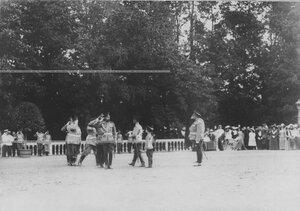 Император Николай ii и цесаревич Алексей здороваются с офицерами свиты во время парада полка.
