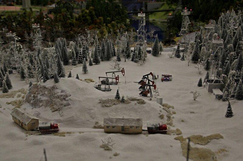 Гранд макет: нефтяное месторождение в зимнем лесу. Станки-качалки, ёлки, сторожевые вышки с прожекторами, две вездехода везут теплушки.