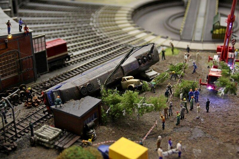 Гранд макет: локомотив сошёл с рельсов рядом с поворотным кругом, повалив деревья и подмяв под себя грузовик и легковой автомобиль. Ликвидация последствий, зеваки и спецтехника