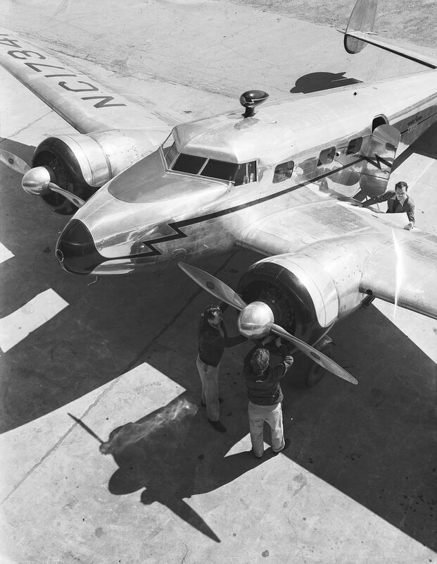 Three men standing next to a Lockheed model 12A Electra Junior, owned by Byrd-Frost, Incorporated, at Dallas Love Field Airport. March 1940