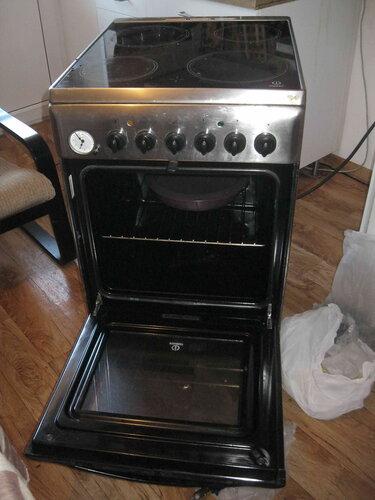 Фото 30. С целью доступа к винтам фронтальной панели электроплиты электрик открыл духовку.