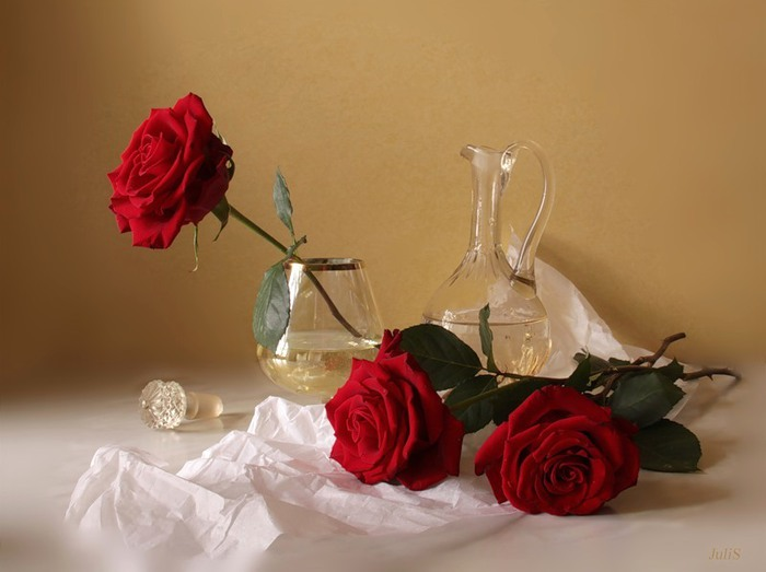 Одна из роз оставлена в бокале, другие лежат на столе