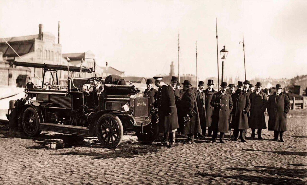 1911. Группа пожарных деятелей осматривает пожарный автомобиль системы Коммер-Кар