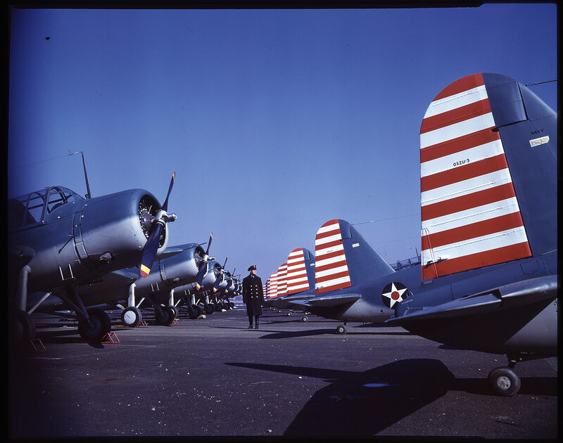 Rear view showing many Vought OS2U-3 Kingfishers lined-up at an unknown depot,  an officer is walking between the aircraft.