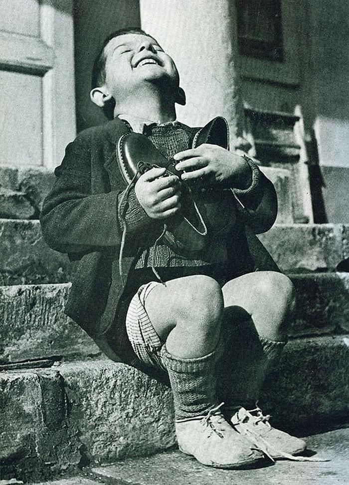 Австрийский мальчик только что получил в подарок новые туфли. Снимок сделан во время Второй мировой войны.