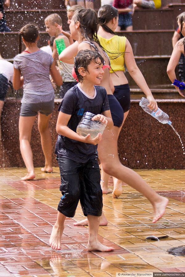 Мальчик с ёмкостью с водой в руках