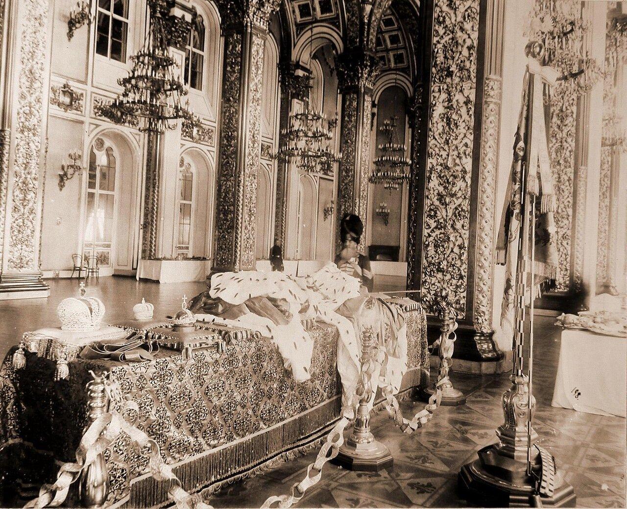 Дворцовый гренадер в Андреевском (Тронном) зале Большого Кремлевского дворца у царских регалий; на столе слева направо Большая и Малая императорские короны, держава, скипетр, порфиры (императорские мантии); у стола