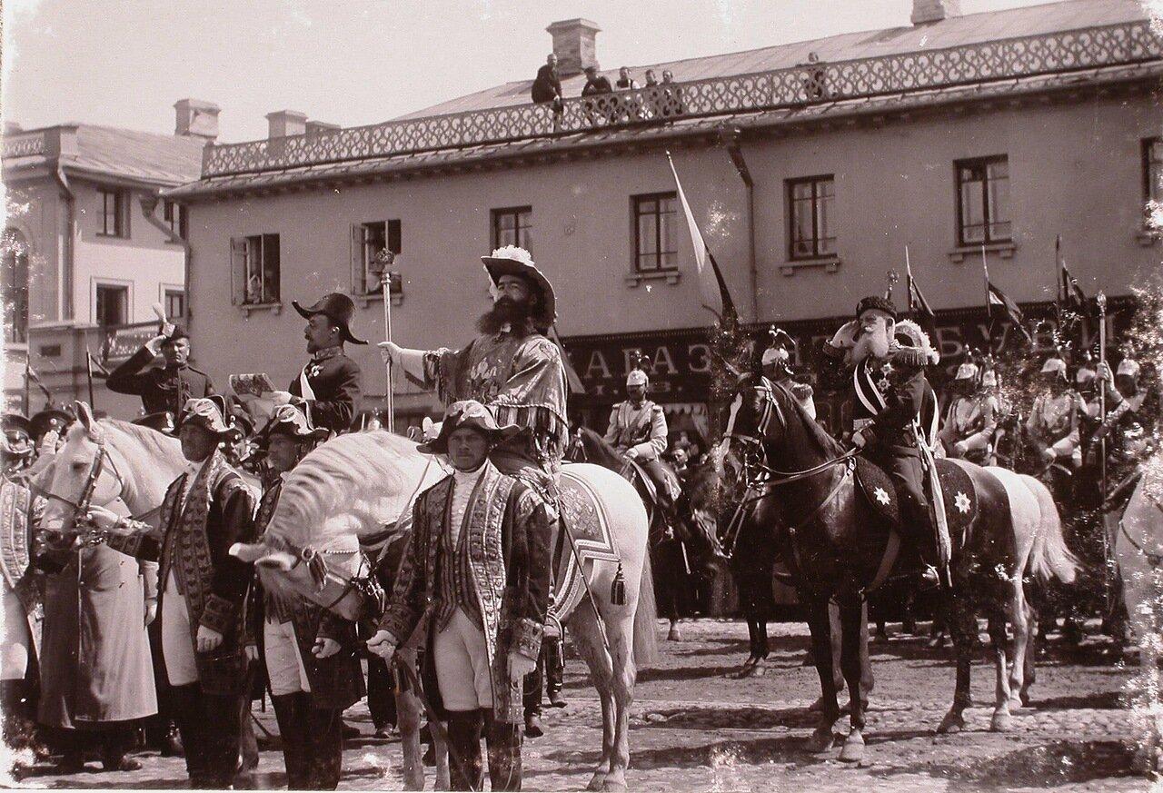 Церемониймейстеры и один из герольдов объявляют горожанам о дне священного коронования на одной из улиц города