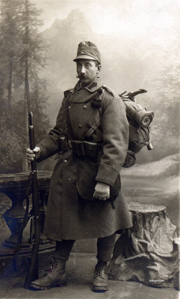 Nothing on reverse.Studio portrait of an Austro-Hungarian infantryman, well equipped for mountain warfare.This fellow is wearing a M1908 high-crowned field-cap with title band, heavy overcoat, standard leather M95 ammunition pouches and rucksack.