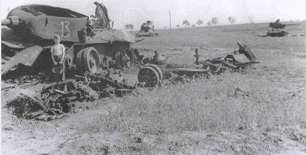Мальчик лет семи на месте прошедшего боя, у взорванного советского танка Т-34-85. Позади видны еще два таких же танка.