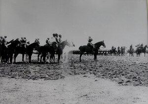 Войска проходят церемониальным маршем мимо императора Николая II и сопровождающих его военных чинов.