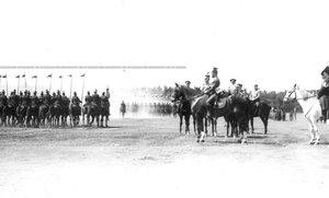 Уланский полк проходит церемониальным маршем мимо императора Николая II и сопровождающих его лиц во время парада.