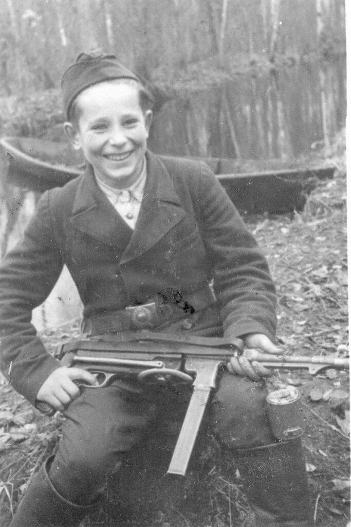Портрет 15-летнего партизана-разведчика Миши Петрова из отряда имени Сталина с трофейным немецким 9-мм пистолетом-пулеметом МР-38. Боец подпоясан солдатским ремнем Вермахта, за сапогом — советская противопехотная граната РГД-33. Белоруссия, 1943 г.