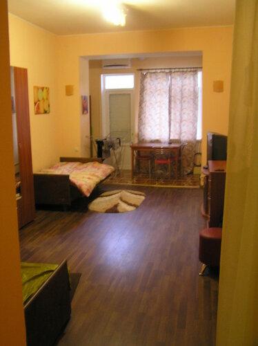 Длинная просторная комната, вид от двери. Пол покрыт коричневым ламинатом. Одесса.