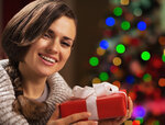 Happy young woman holding christmas present box in front of chri