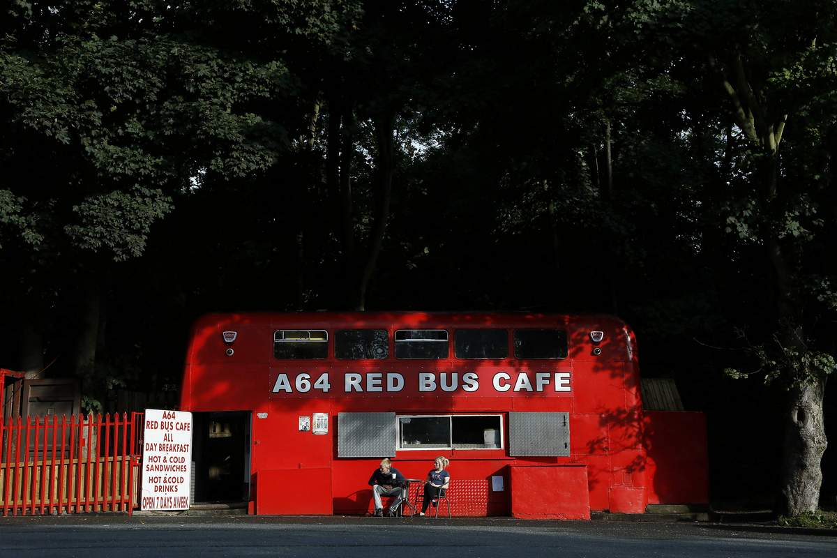 Jay Grey and his sister Vicky wait outside their roadside double-decker cafe, the Red Bus Cafe along the A64 near Thorner, northern England