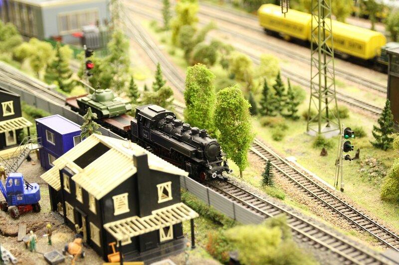 Гранд макет: старинный чёрный паровоз тащит по железнодорожным путям платформу с танком. Семафоры показывают правильный цвет