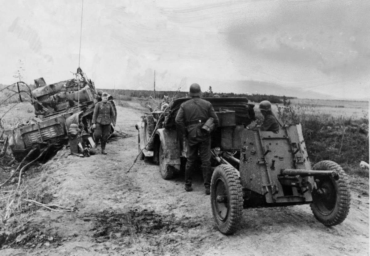 1941. Немецкие артиллеристы осматривают останки тяжелого артиллерийского тягача «Ворошиловец»