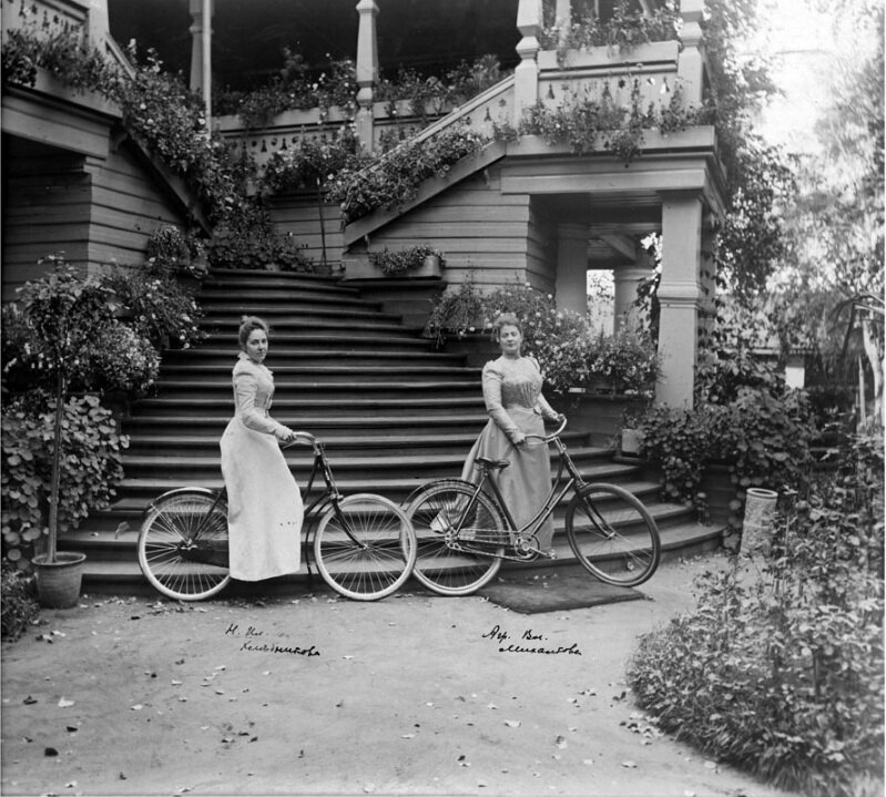 А. Михалкова и Н. Хлебникова с велосипедами на лестнице дома в усадьбе Петровское.