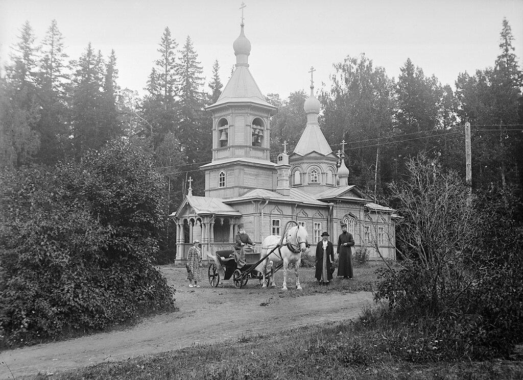Люди и конный экипаж возле деревянной церкви