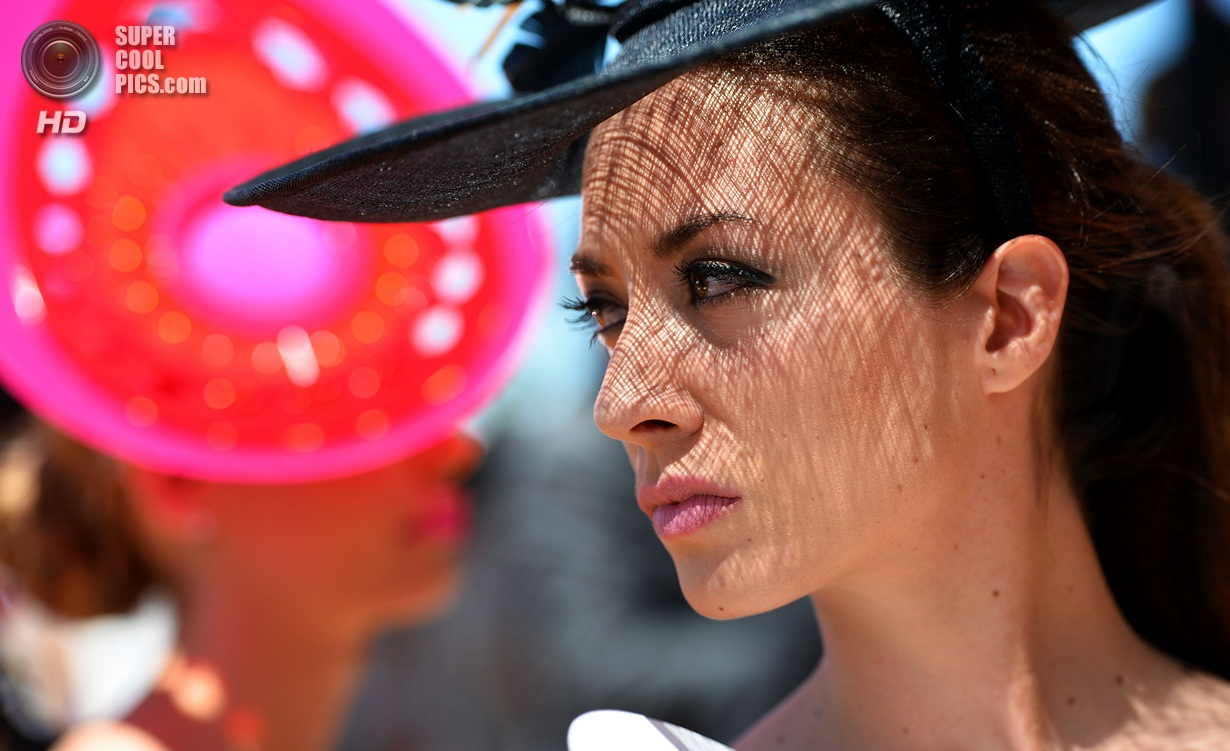 A race-goer models her outfit for the Fa