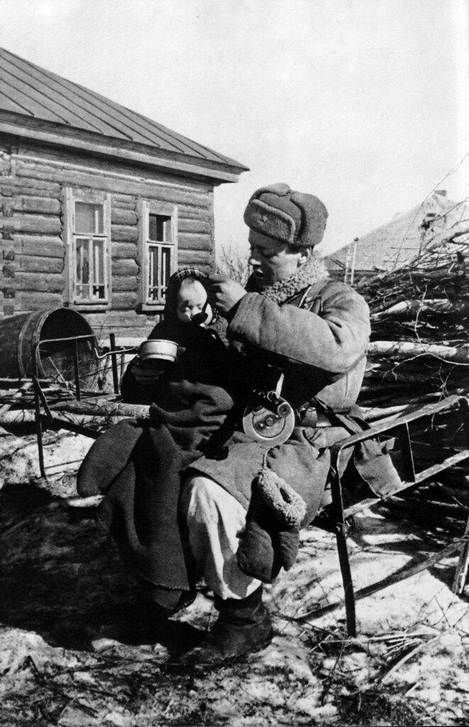 «Всех угнали фашисты». Старший сержант Моисеев — командир отдельной артиллерийской разведки 2-го дивизиона 4-й батареи 308-го полка кормит двухлетнюю девочку Валю, найденную им в одной из пустых изб деревни Извеково. Смоленская область, Вяземский район, 1