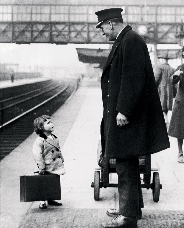� very young passenger asks a station attendant for directions, on the railway platform at bristol, england, 1936