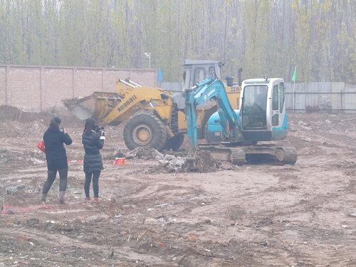 Экскаватор роет яму под фундамент, всё в дыму от фейерверка