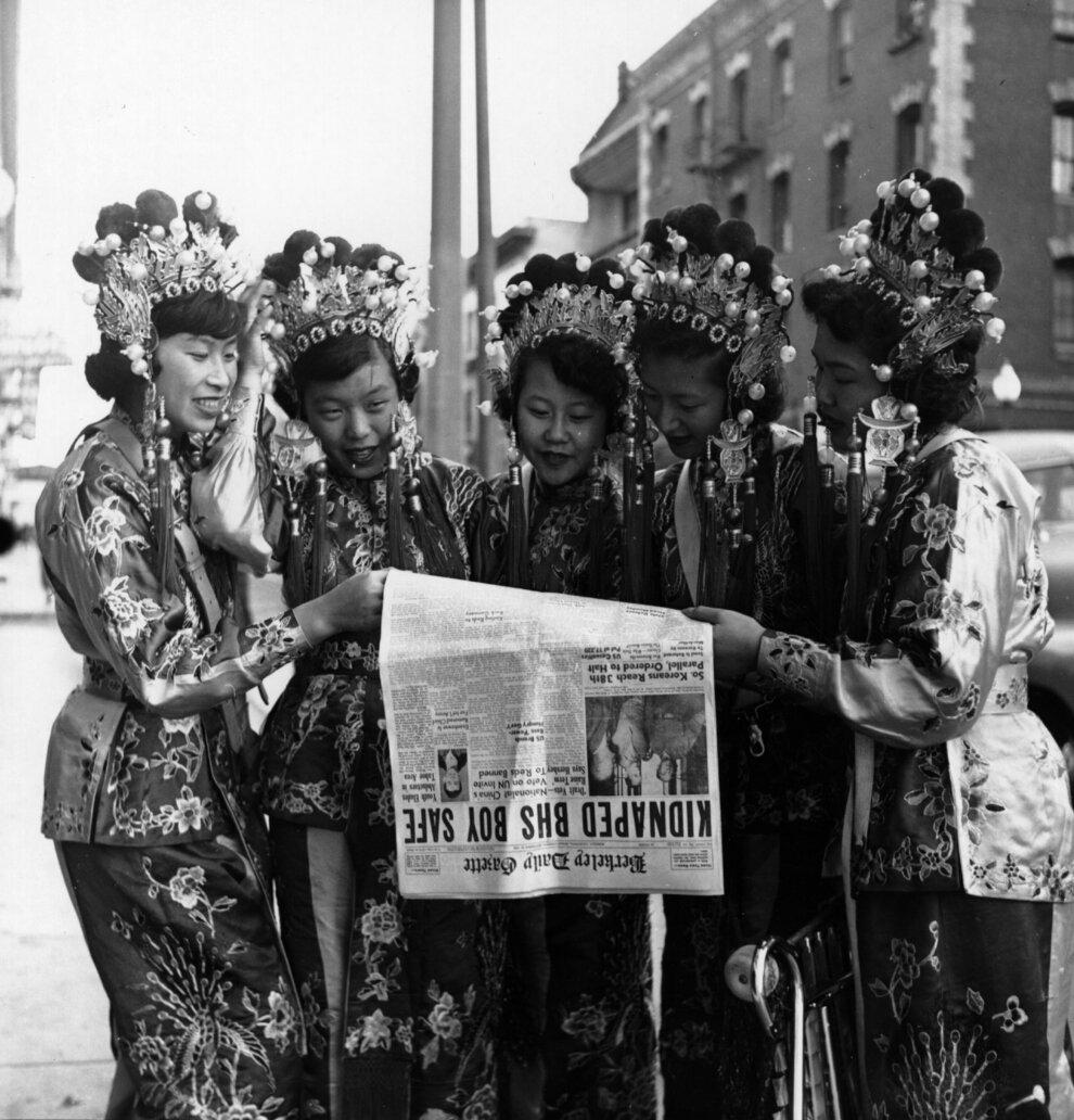 Пять женщин, одетых в традиционную китайскую одежду читают заголовки дня.