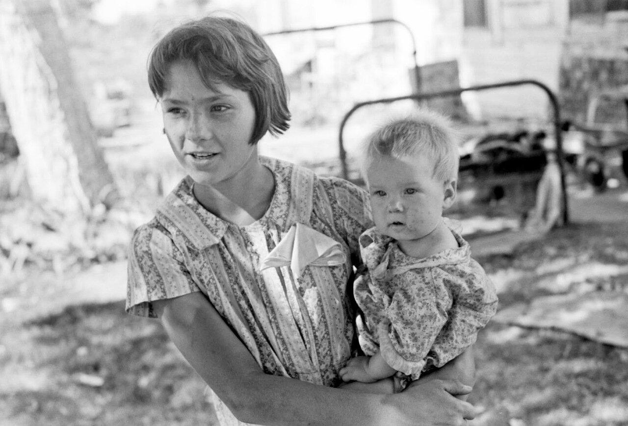 Молодая девушка, держащая младшего братика на руках в лагере, Оклахома-Сити, 1939