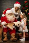 Santa Claus sitting at home with cute little girl and her mother and reading letter