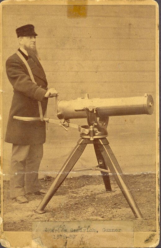 Charles Goodrich stands behind a Model 1883 Gatling Gun on a tripod with one hand on the crank. Another piece attaches his waist to the tripod.
